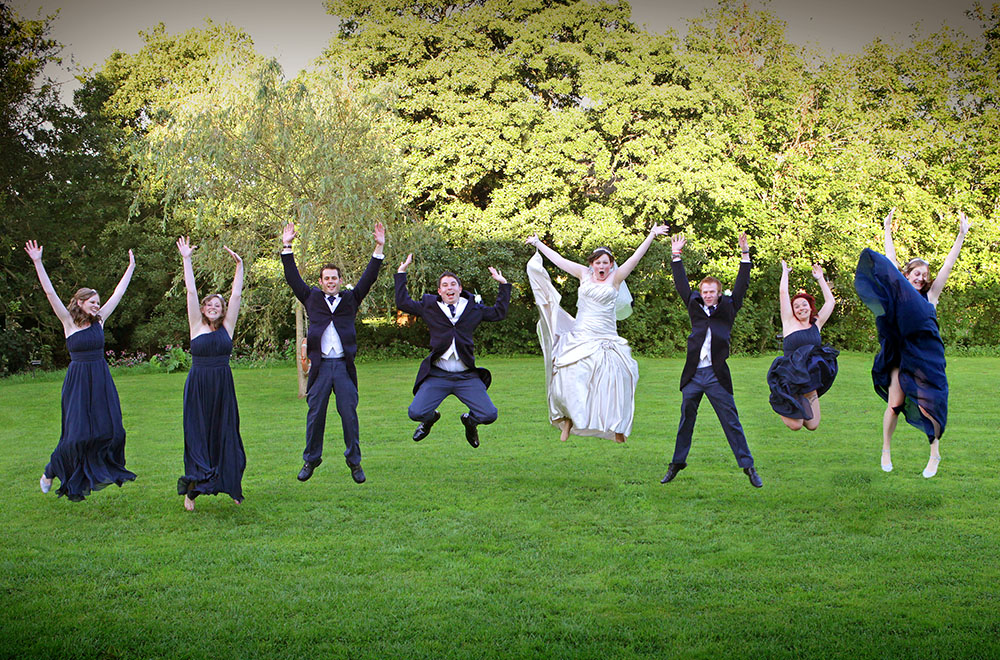 Bride and groom with guests jumping in air